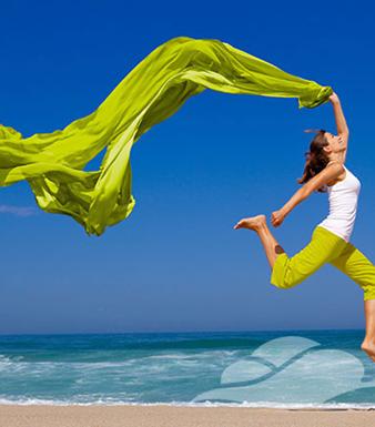 Uitbundige vrouw aan het strand met groene wapperende doek